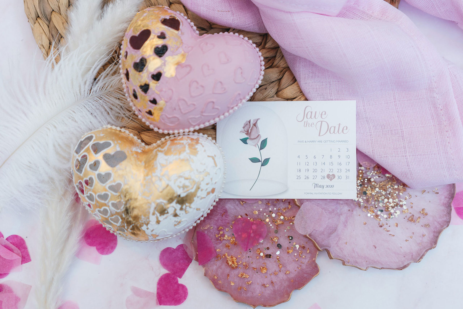 Pink and white Valentine's Day themes flat lay with 2 carved eggs in heart shapes, a wedding save the date card and 2 pink resin coaster on a wicker placemat with confetti and pink fabric around it.