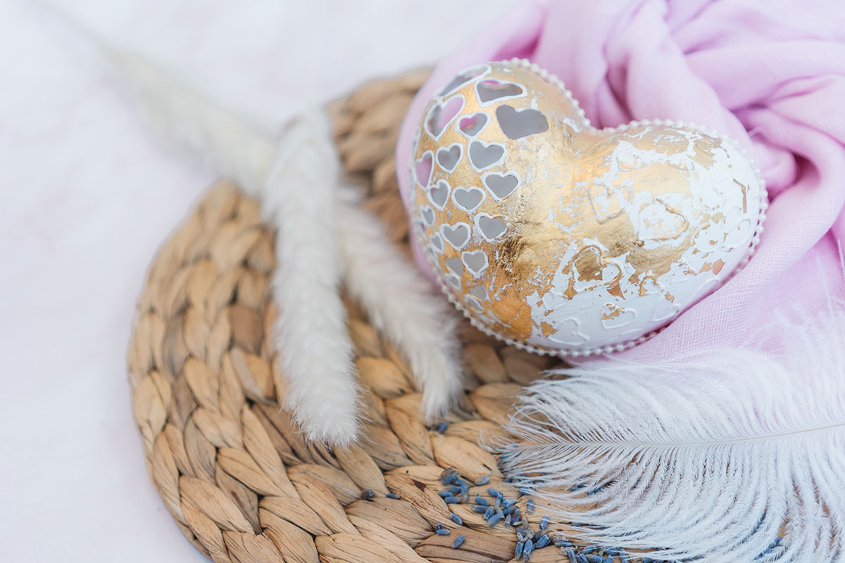 A white and gold hand carved egg on a wicker placemat surround by lavender, pampas grass, a feather and pink fabric