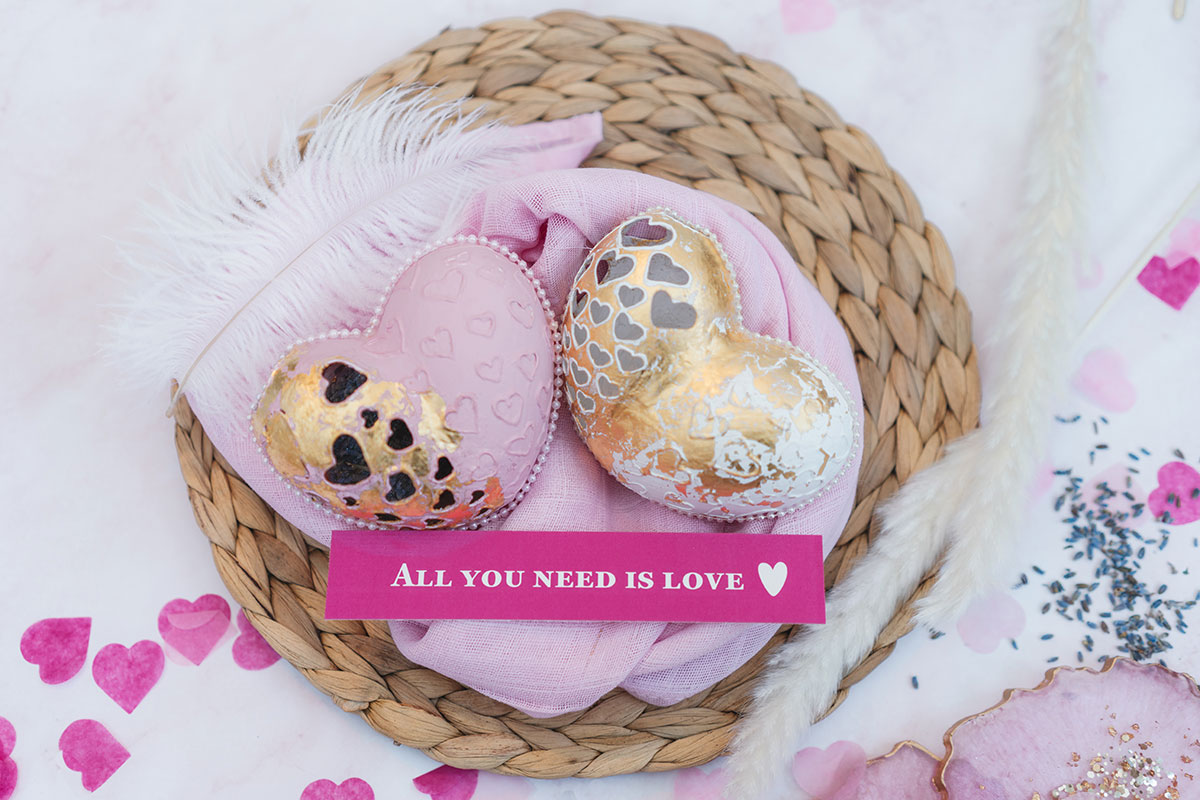 2 heart shaped carved eggs in pink and white with a pink place setting that says 'all you need is love' on a wicker placemat with pink fabric, pampas grass and confetti.